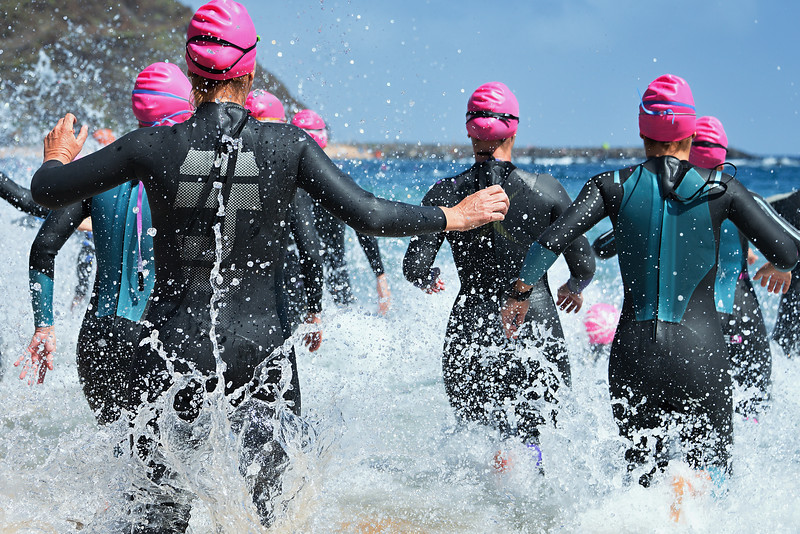 Group triathlon participants running into the water for swim portion of race,splash of water and athletes running.