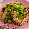 Restaurant served healthy food, salad closeup. Turkey salad with orange, vegetables and lettuce on pink plate. Appetizing dish served with sauce, dinner meal. Selective focus