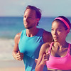 Couple athletes runners running on beach. Interracial young adults asian woman, caucasian man, train