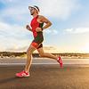 Triathlon - Triathlete man running in triathlon suit training for ironman race. Male runner exercisi