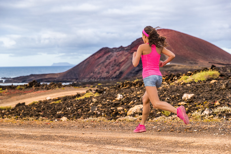 Trail runner athlete woman running training cardio on rocky mountain path on long distance endurance