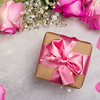 Beautiful pink roses and gift box with pink bow on wooden background. St Valentines day or mothers day concept. Copy space