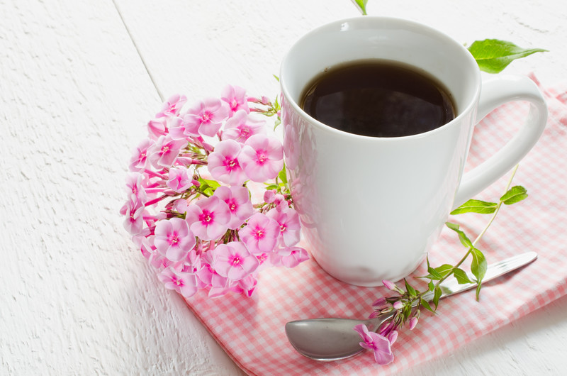 Morning coffee or cup of tea with pink flowers on wooden white rustic table. Selective Focus.