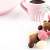 olorful handmade candies in glass jar and pink cup of coffee on white background with copy space. Valentines day concept
