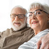Portrait of mature lady and old happy man hugging. Focus on woman while they are laughing sitting on couch at home