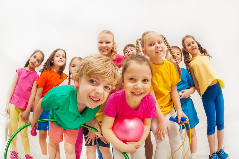 Portrait of cute kids in sportswear with female gymnastics coach, holding sports equipment, standing together in gym, looking at camera
