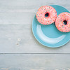 Top view of two pink donuts on gray wooden background with copy space. Colorful donuts on plate with copyspace. Glazed doughnuts with sprinkles on grey wooden table. Smile sign, good morning concept