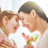 Happy mother's day! Child daughter congratulates mom and gives her flowers tulips and postcard. Mum
