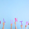 People putting hands in air together with word made of paper letters on light background. Volunteeri