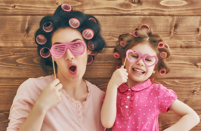 Funny family! Mother and her child daughter girl with a paper accessories. Beauty funny girl holding