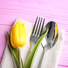 Table setting with silver cutlery and napkin on pink wooden background