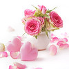bouquet of flowers in a vase on white background and pink hearts. valentine's day decoration
