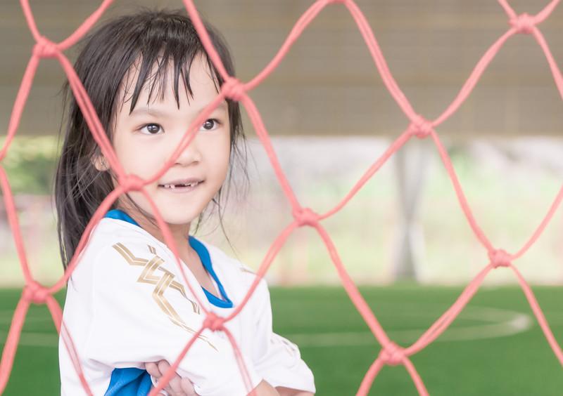 Soccer kid girl is stand inside a soccer goal on soccer training field
