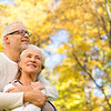 family, age, season and people concept - happy senior couple hugging over autumn trees background