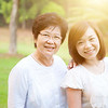 Portrait of attractive Asian elderly mother and daughter, senior adult woman and grown child. Outdoo