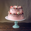 Pink Cake Rustic With Berries, Marshmallows And Macaroons On Top.