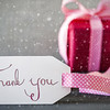 Label With English Calligraphy Thank You. Pink Gift Or Present With Gray Cement Background With Snowflakes