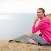 A sporty woman with a sweet smile, a brunette, hair braided in a braid, full lips, wearing gray sports pants, pink sneakers and a pink sports jacket, doing warm-up exercises on a rocky blue ocean shore, sitting on an athletic rug
