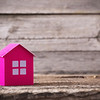 the pink paper house on wooden background