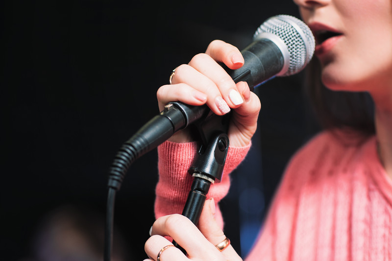 Microphone and unrecognizable female singer close up. Cropped image of female singer in pink dress , singing into a microphone, holding mic with two hands. Copyspace