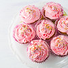 Pink cupcakes on cake stand top view. Birthday cupcake with whipped cream. Homemade cupcakes served for party. Birthday background.