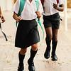 Smiling school kids running in corridor at school