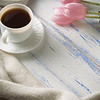 Pink Tulips, White Scarf, Coffee Cup And Gift Box On A White Wooden Background
