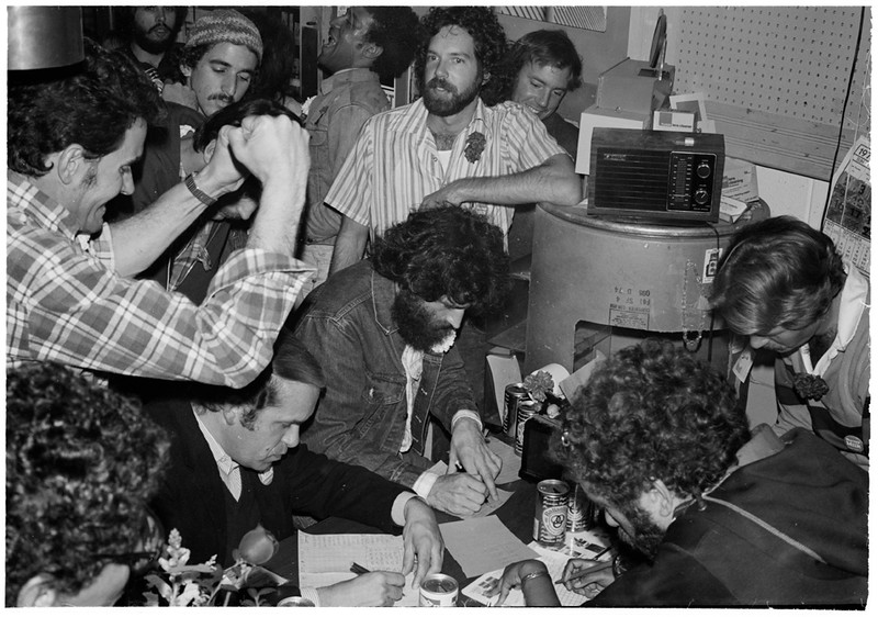 Campaign supporters cheering radio telecast Election Returns on thee night of Harvey Milk's election to the SF Board of Supervisors as one of the nation's first openly gay elected officials. November 8, 1977<br /> L to R: Harry Britt, Wayne Friday ,seated>, david Weissman,