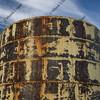 old rusty grain bin against partially cloudy sky