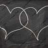 two heart speech bubbles on blackboard