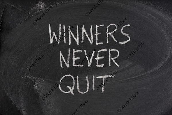 winners never quit phrase on blackboard