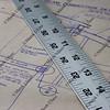 metal ruler over old house blueprint