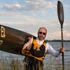 paddler carrying a racing kayak with number thirteen