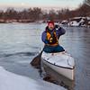 paddling canoe on a winter river