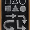 geometrical shapes and arrow - white chalk on blackboard