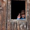 cowboy in a dark window of old barn