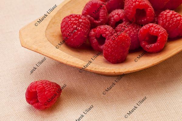 red raspberries in wooden bowl