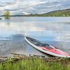 red SUP paddleboard on lake shore