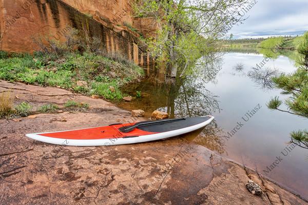 stand up paddleborad on lake shore