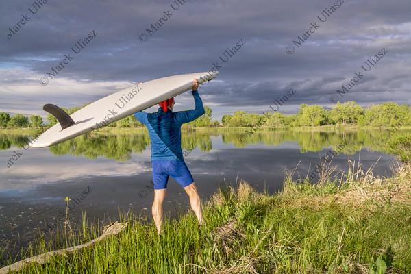 SUP paddler carrying paddleboard