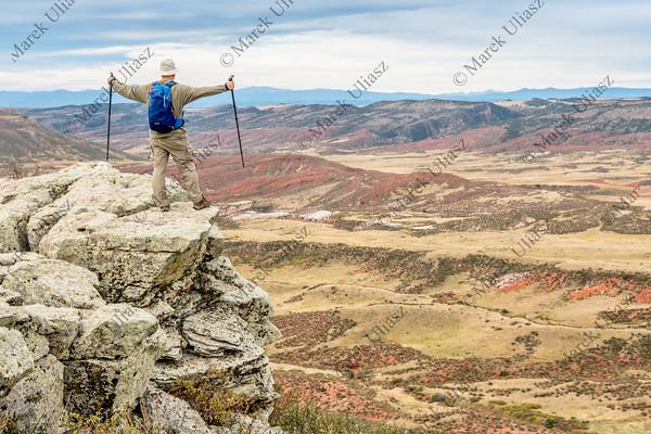 hiker on rocky cliff overlooking valley