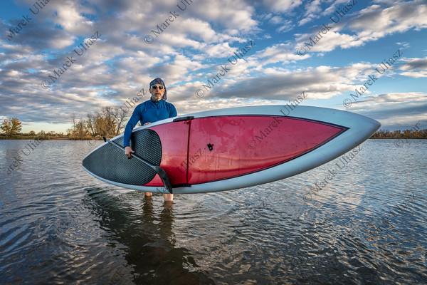 launching stand up paddleboard on lake