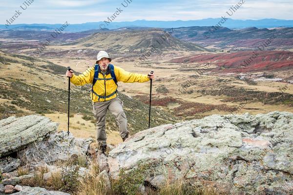 senior male hiker on rocky cliff