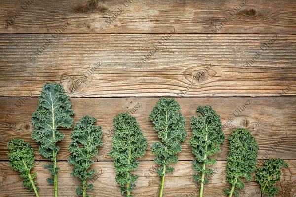 green kale leaves on wood