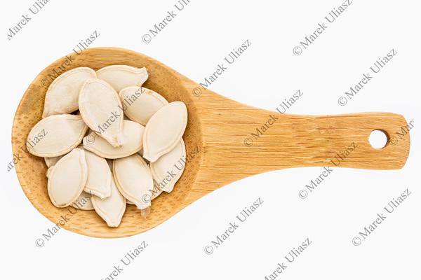 pumpkin seeds on wooden spoon