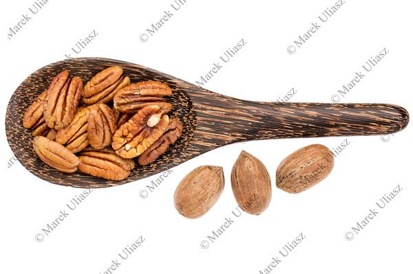 pecan nuts on wooden spoon