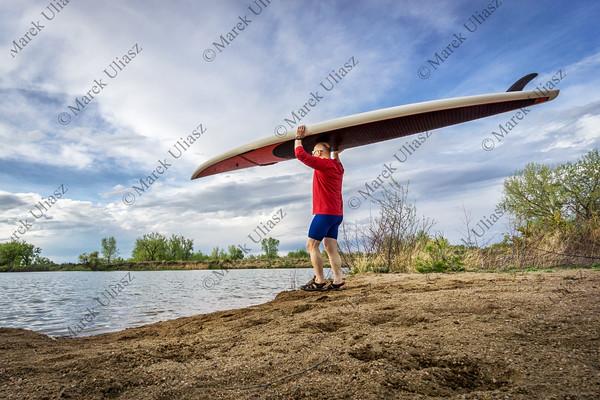 senior paddler carrying paddleboard