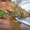 canoe paddler and sandstone cliff