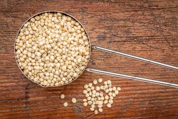 white sorghum grain in a metal scoop