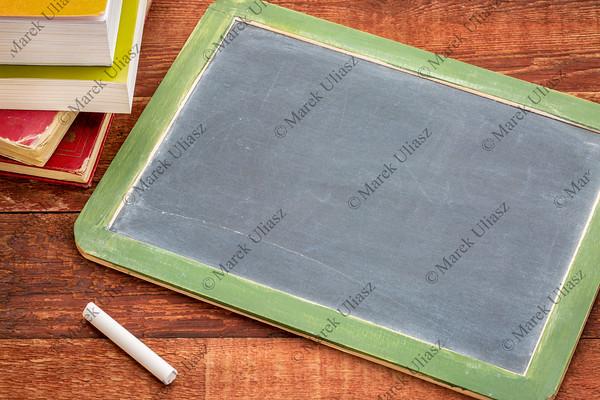 blank slate blackboard with chalk and books
